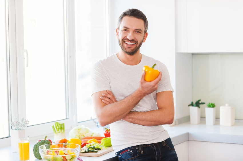 Healthy food is healthy life. Handsome young man holding fresh yellow pepper and smiling while standing in the kitchen