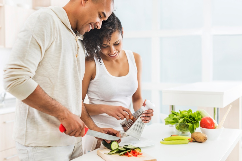 African American couple preparing salad in the kitchen.
