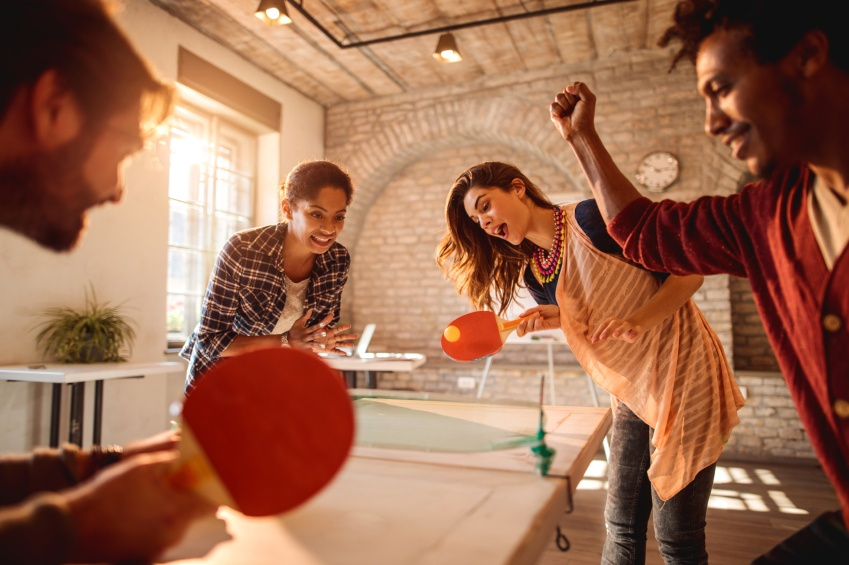 Happy businesswomen playing table tennis against businessmen at casual office.