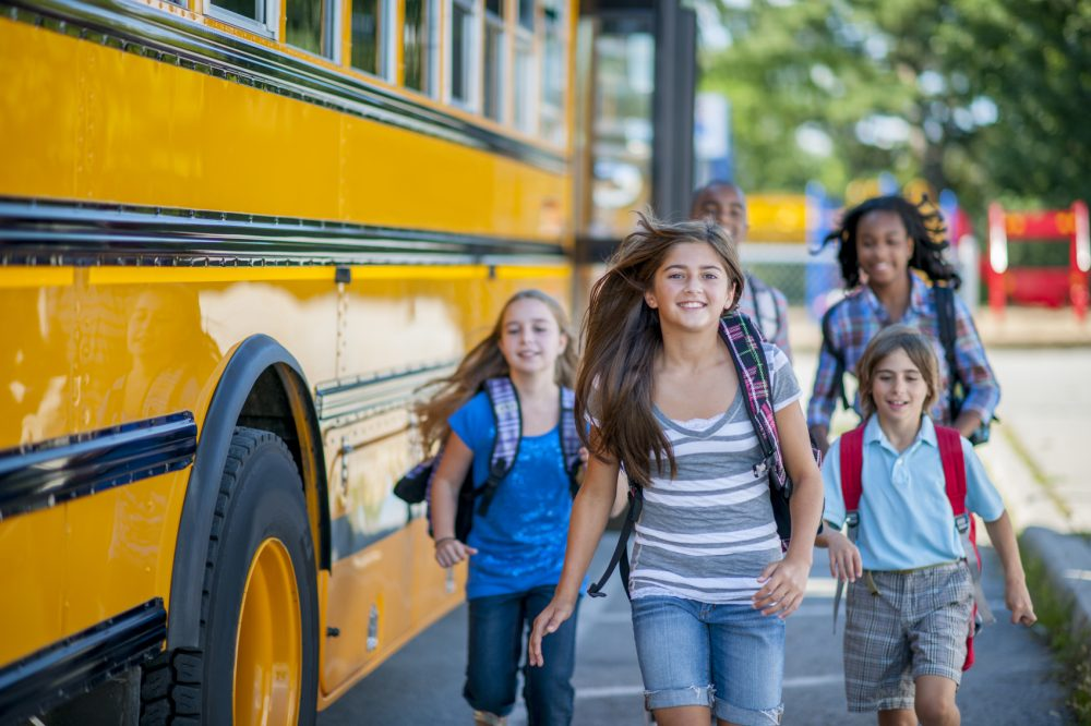 A multi-ethnic group of elementary age children are running from the bus to class. They are smiling and looking at the camera.