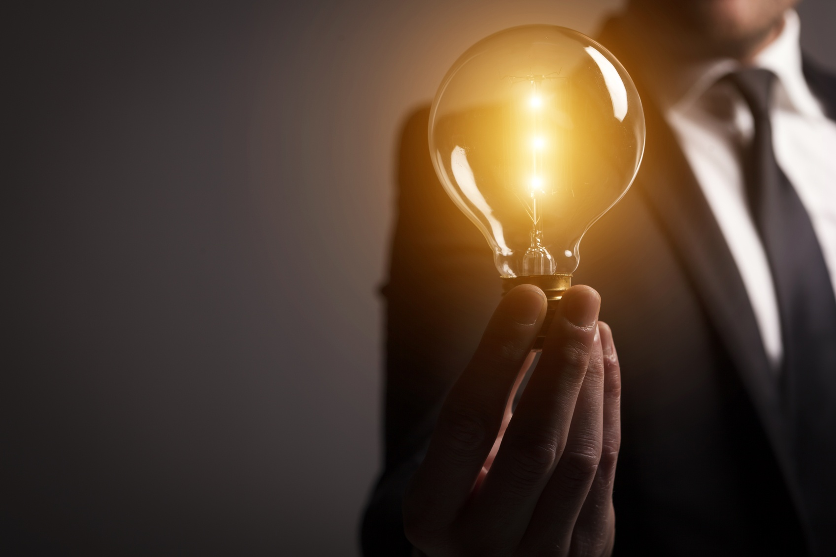 Businessman holding a glowing light bulb