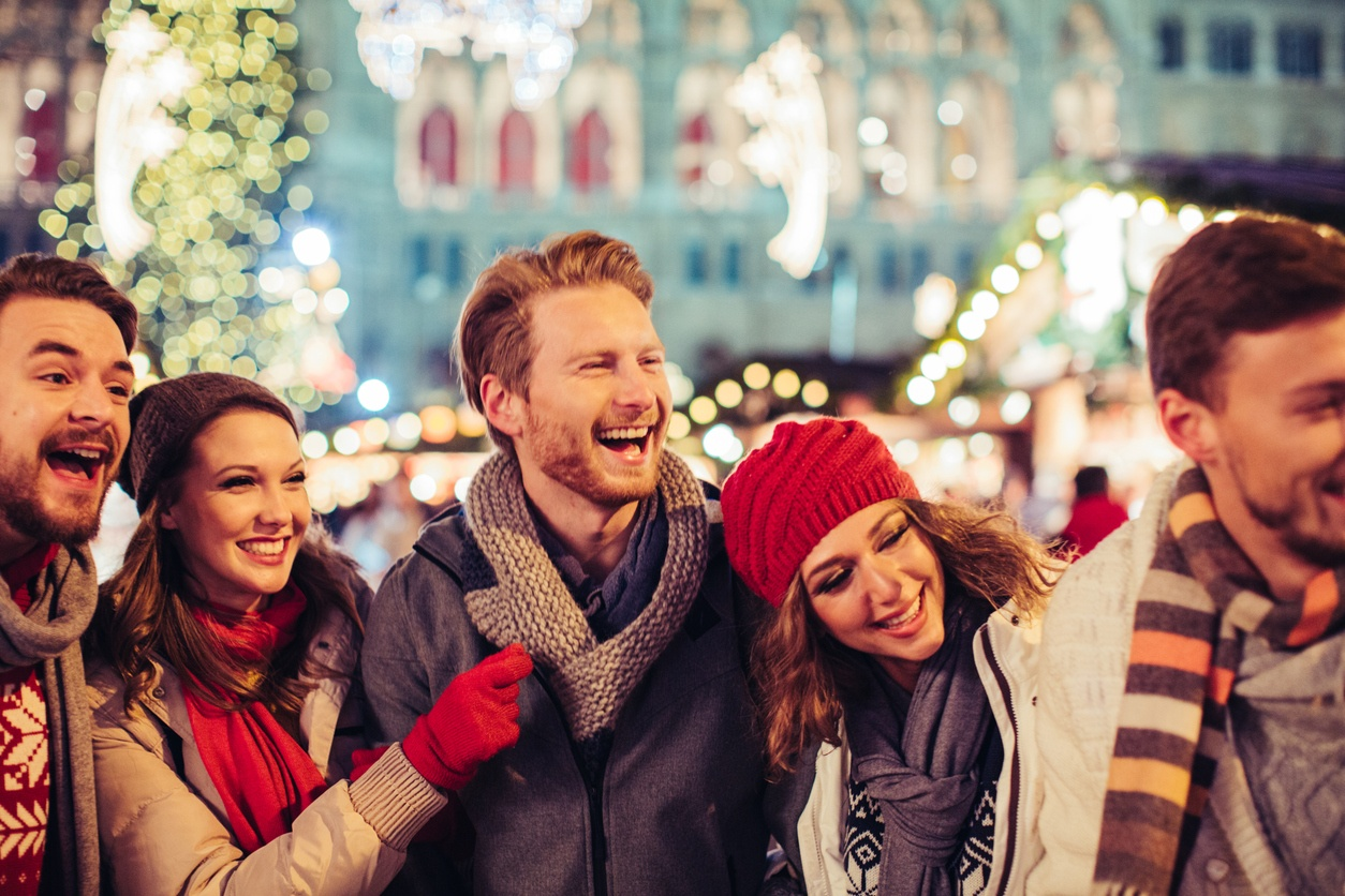 Young group of friends having fun outdoors at winter. Wearing warm clothes, hats and scarfs.Visiting christmas market in Vienna, Austria. Everything is decorated with festive string lights. Evening or night with beautiful yellow lights lightning the scenes.